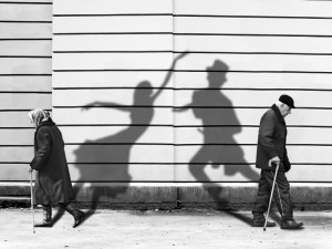 older man and woman walking projecting shadows
