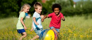 Trio of Children with Beachball in Meadow
